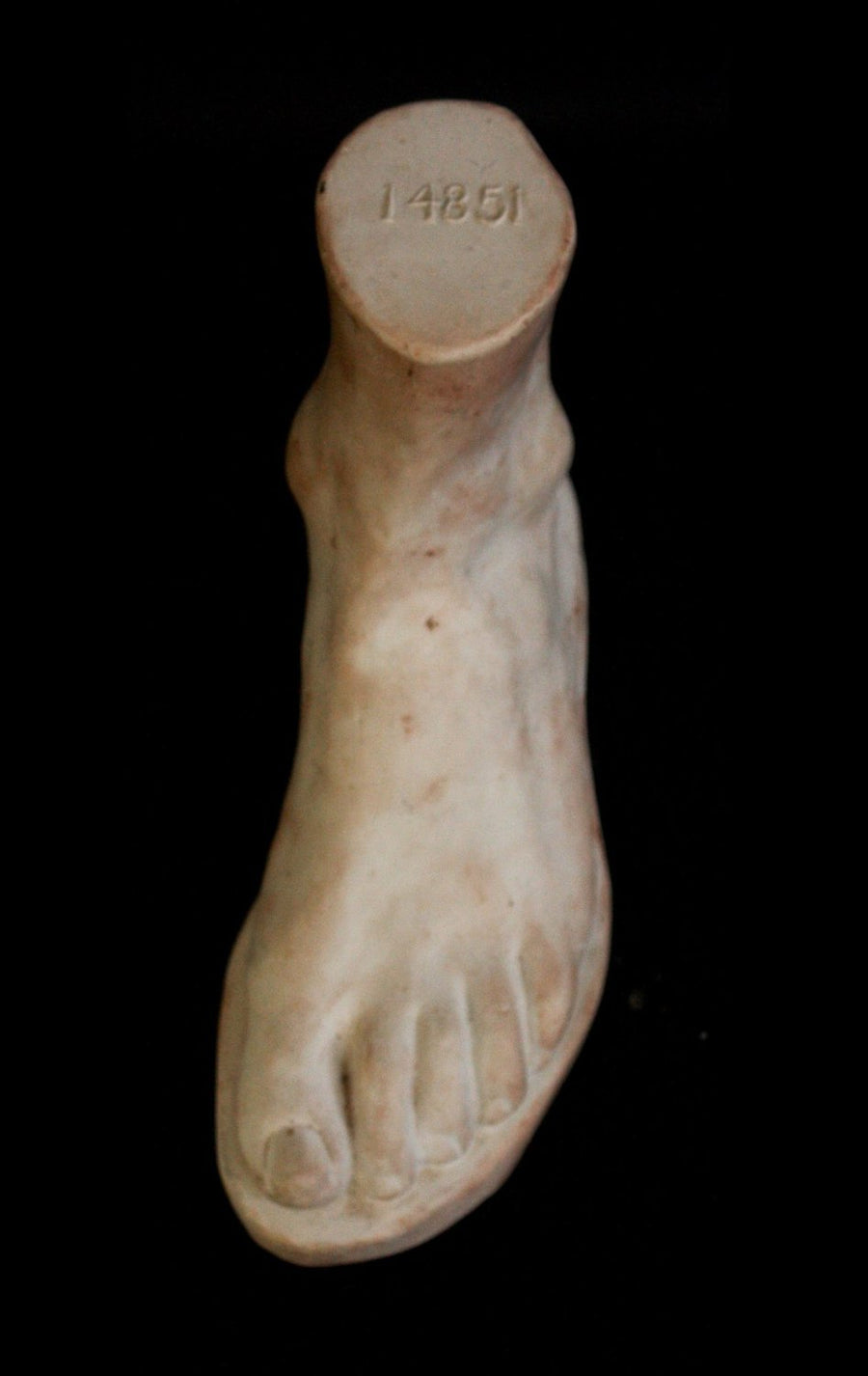 Photo of plaster cast male foot sculpture from the top on a black background