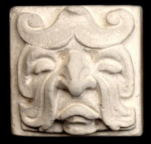 Photo of square tile sculpture of sad face made of leaves