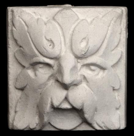 Photo of square tile sculpture of face made of leaves