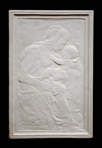 photo of plaster cast sculpture relief of the Madonna holding baby Jesus on her lap on black background