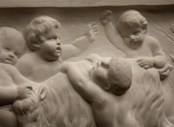 closeup photo of plaster cast relief sculpture of several putti around a goat celebrating the god Bacchus