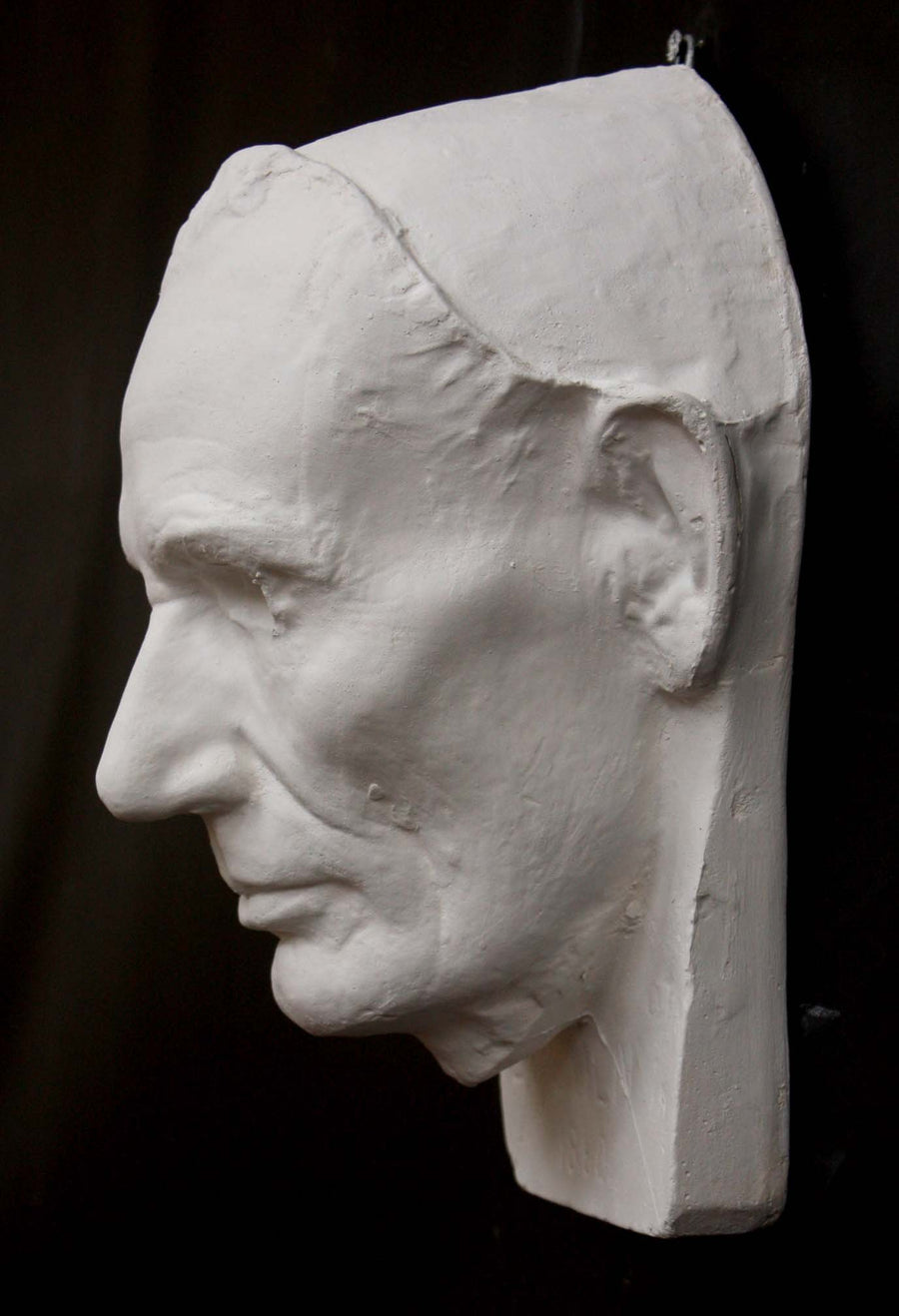 Photo of plaster cast sculpture of life mask of Abraham Lincoln from a side view on a black background