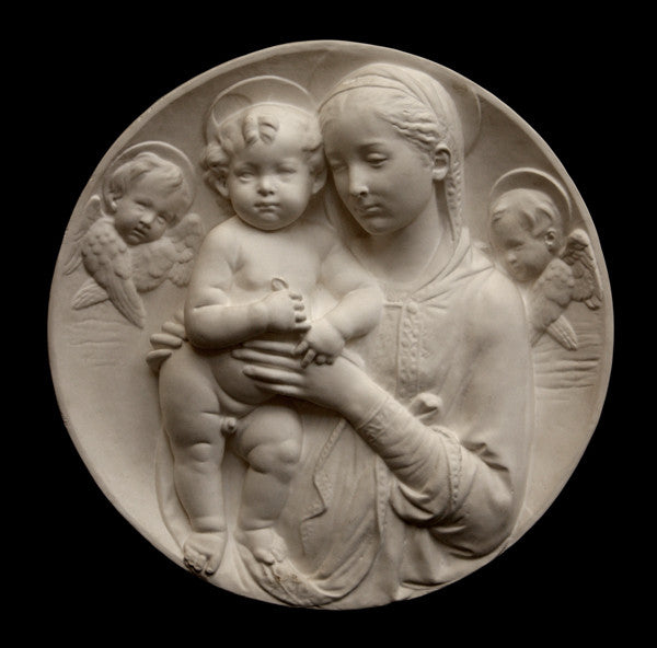 photo of plaster cast sculpture relief of the Madonna holding baby Jesus and angels in the background on a black background