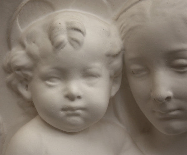closeup photo of plaster cast sculpture relief of the Madonna holding baby Jesus