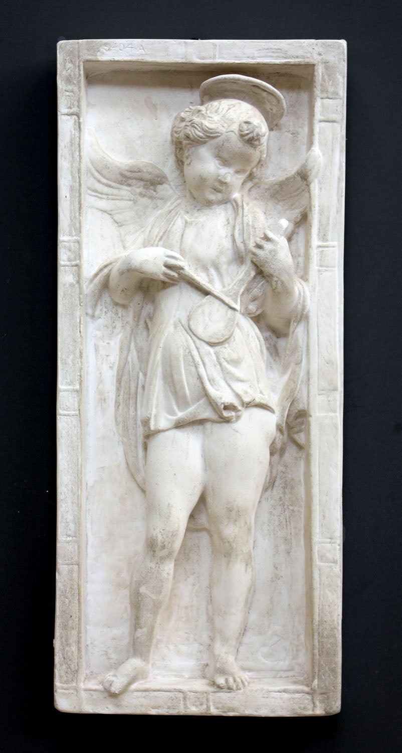 photo of plaster cast relief sculpture with angel playing a lyre on a dark gray background