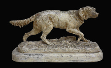 photo of plaster cast sculpture of dog walking on ground on a black background