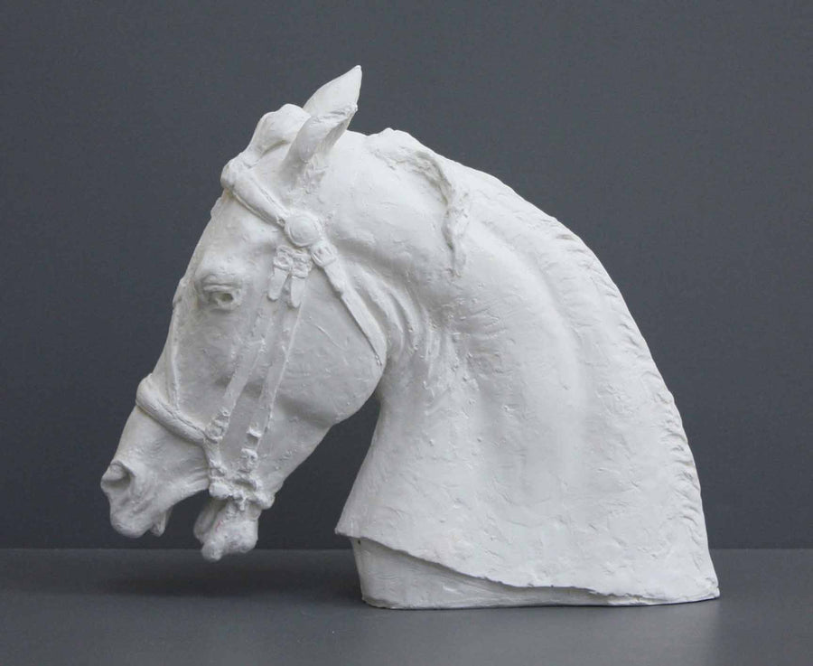 photo of plaster cast of horse head with bridle on a gray background