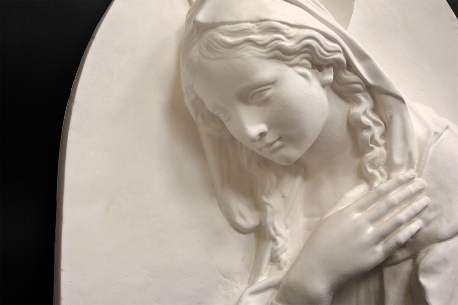 photo of plaster cast sculpture relief of the Madonna leaning over with her right hand crossed over her chest and a halo above her head on a black background