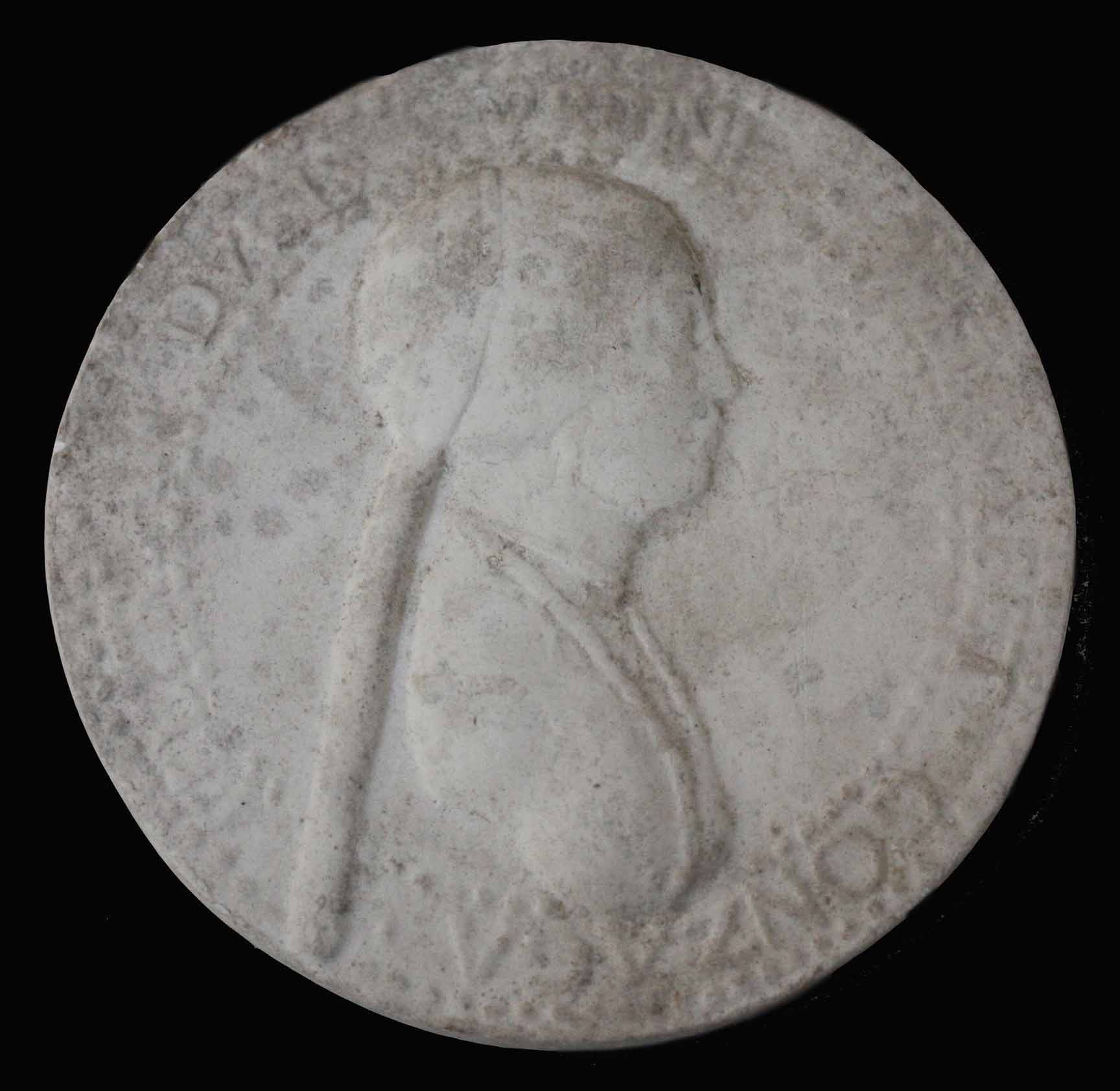 photo of plaster cast of small medallion with female portrait profile on black background