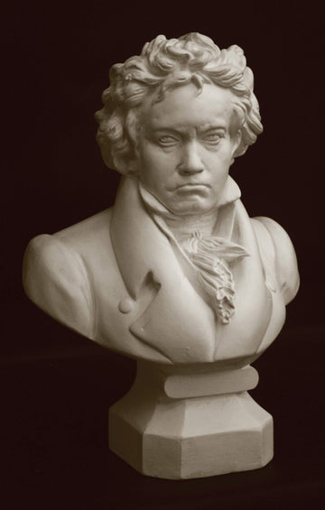 photo with black background of plaster cast sculpture of male bust of Ludwig van Beethoven in dress coat