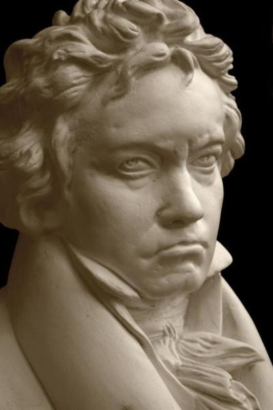 closeup photo with black background of plaster cast sculpture of male bust of Ludwig van Beethoven in dress coat and ruffled necktie