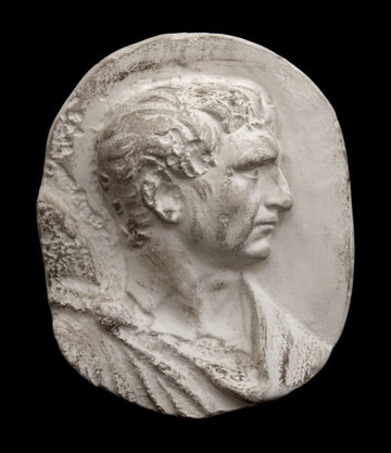 photo of plaster cast sculpture relief of male head and top of toga with a black background