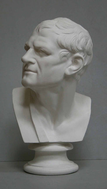photo of plaster cast bust of man with head turned to his right and a sash on his right shoulder on a gray background