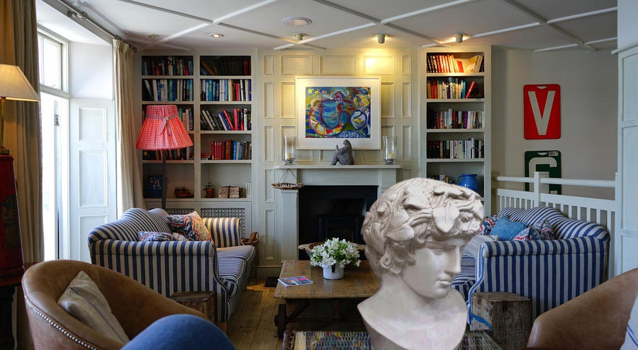 Photo of a colorful living room with blue striped sofas, fireplace, and bookshelves and a plaster cast sculpture of male head of Antinous with crown of leaves in the foreground