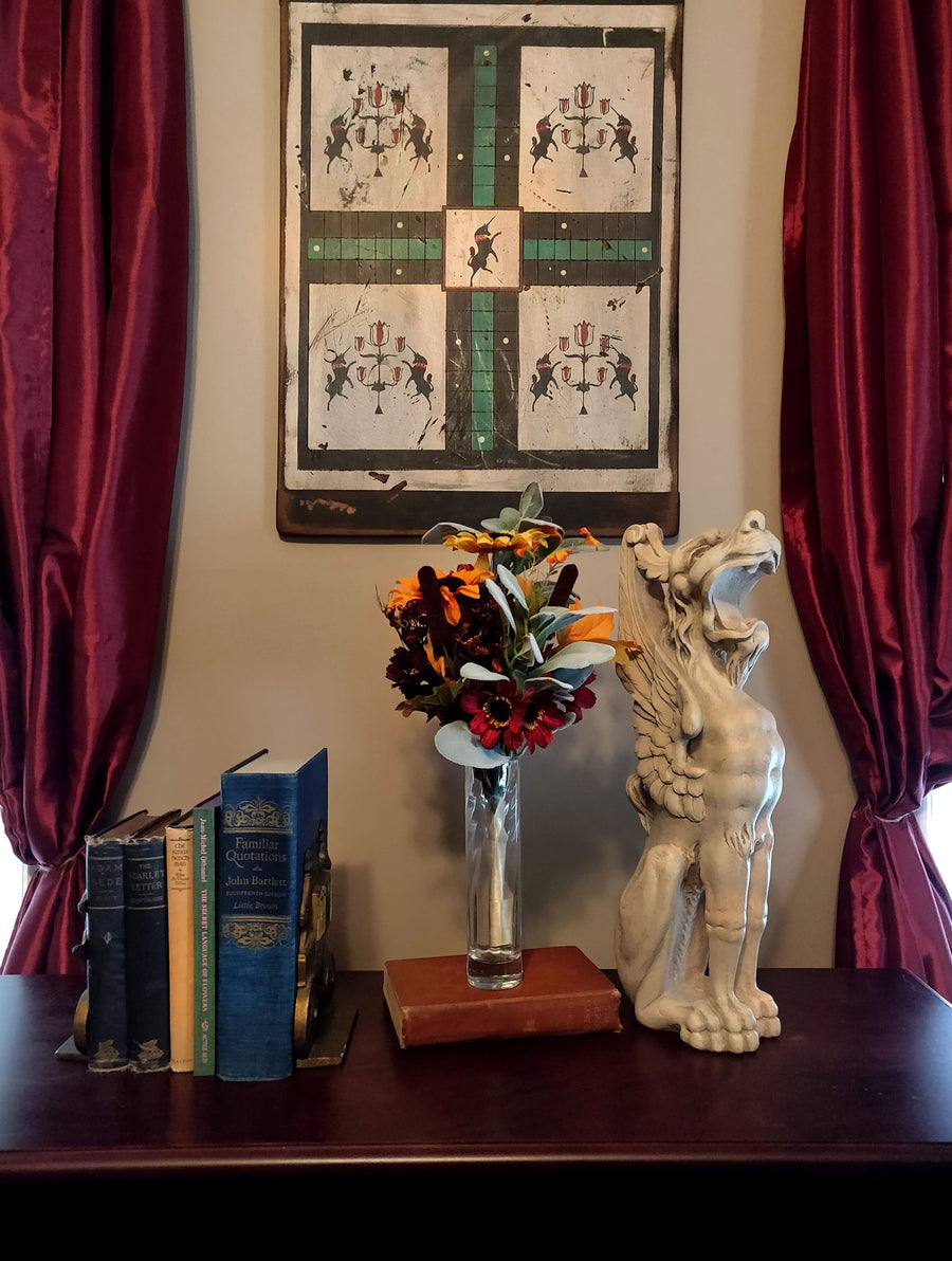 photo of plaster cast sculpture of ornamental seated winged lion on a dark sofa table with antique books and flowers, red curtains behind, and painting on wall
