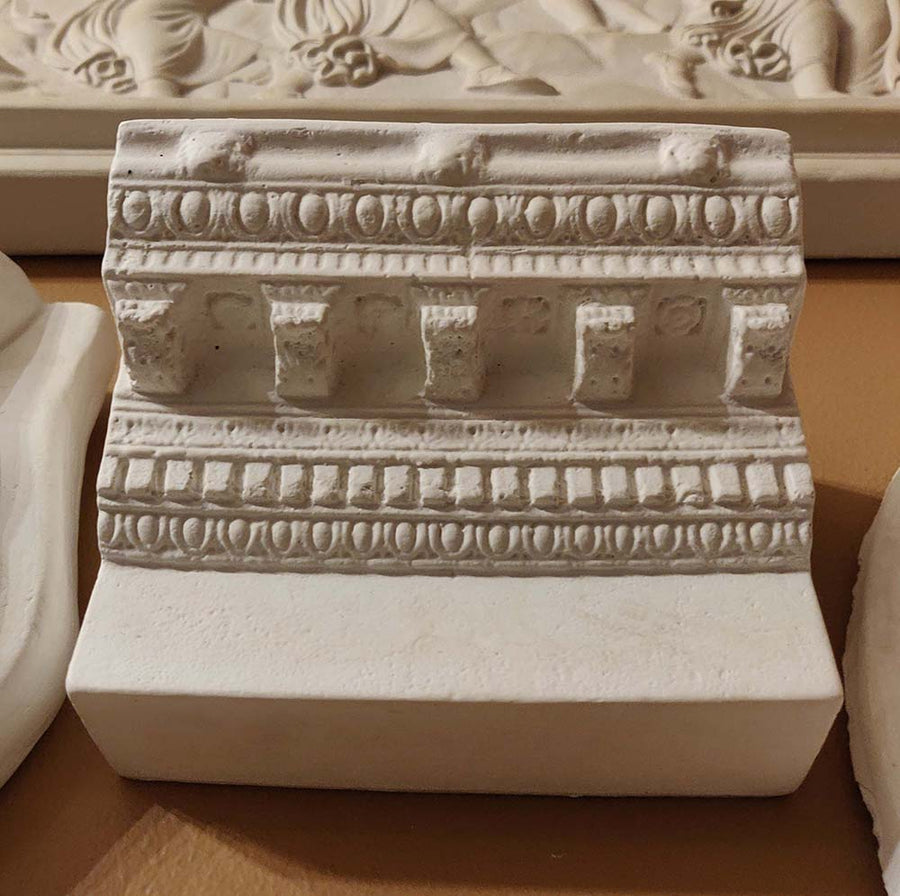 Photo of plaster cast of ornamental architectural detail on gold wall with nearby plaster casts