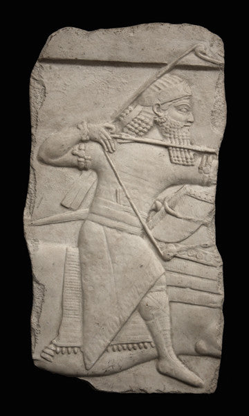 photo of plaster cast relief sculpture of King Ashurbanipal on horseback (only midsection of horse visible) and aiming an arrow in front of him on a black background