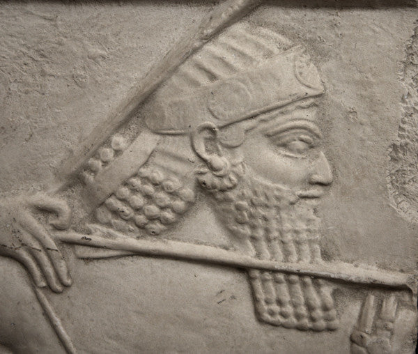 closeup photo of plaster cast relief sculpture of King Ashurbanipal on horseback and aiming an arrow in front of him