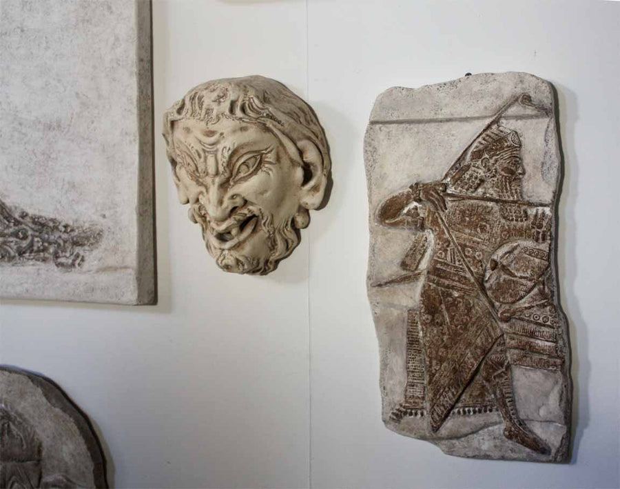 Photo of plaster cast sculpture of ancient sculpture relief and plaster casts of other sculptures on a white gallery wall
