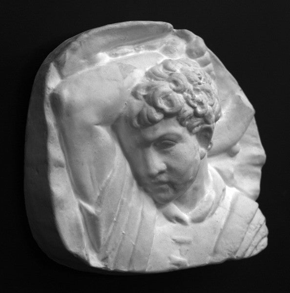 photo of plaster cast sculpture relief of upper body of male with arm raised behind head and holding a hammer with a black background