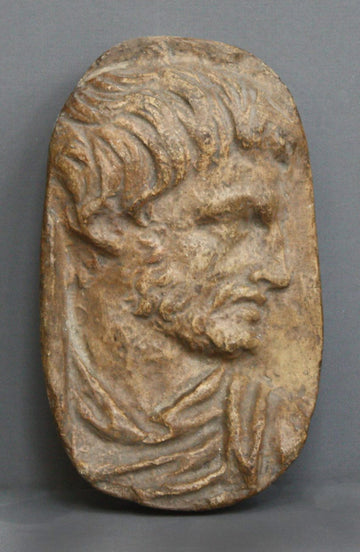 photo of plaster cast sculpture relief of male head with top of toga on a gray background