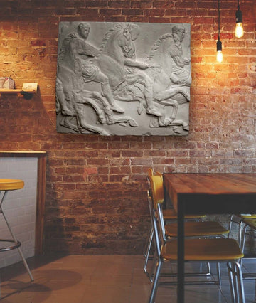 Photo of plaster cast sculpture of men on horses Parthenon Frieze on brick wall with table and chairs on right and bar on left, cropped