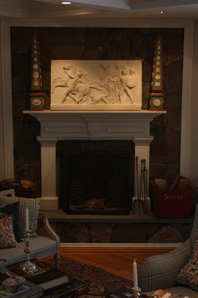photo of plaster cast relief of men, some with armor, horses, and a dog over a fireplace with a stone wall