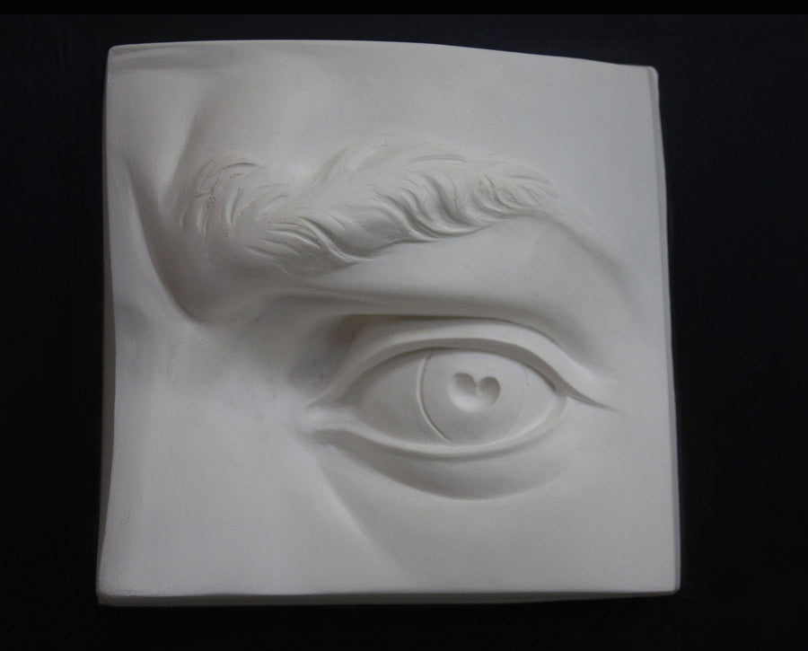 photo with black background of plaster cast of sculpted portion of face with left eye