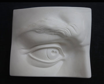 photo with black background of plaster cast of sculpted portion of face with right eye