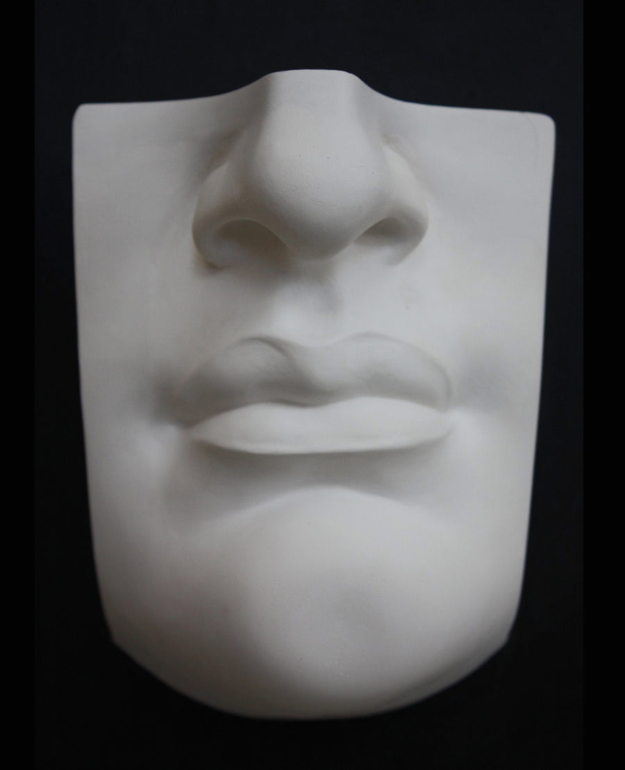 photo with black background of plaster cast of sculpted portion of face with mouth and nose