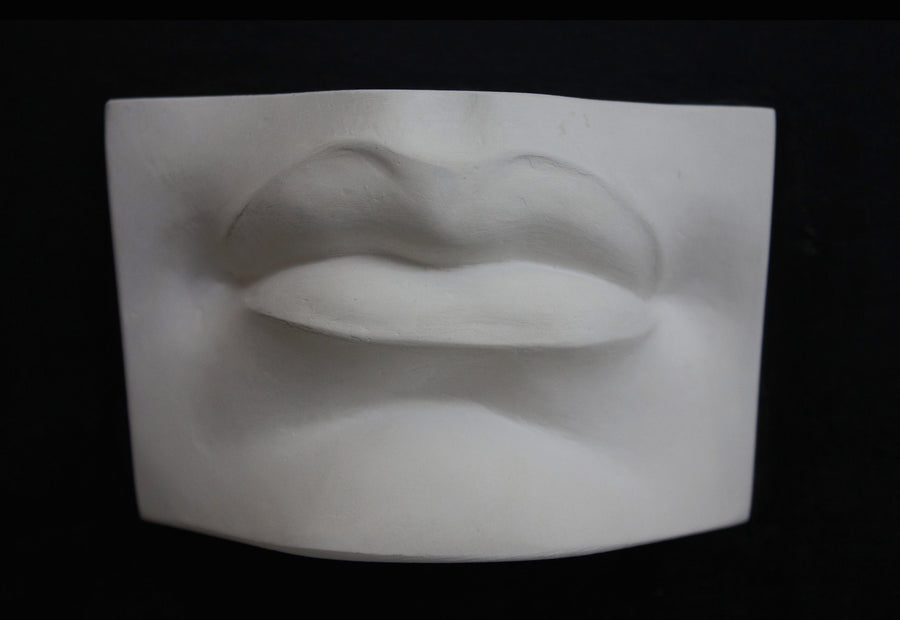 photo with black background of plaster cast of sculpted mouth
