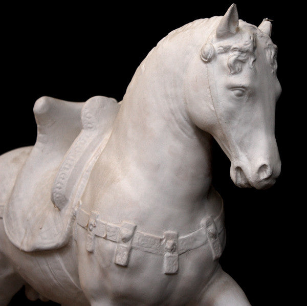 Photo of a sculpture of a plaster horse on a black background