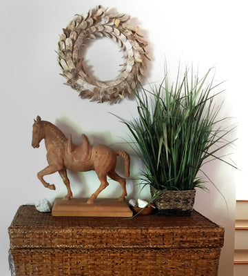 Photo of a plaster cast of a horse with a terra cotta finish on a wicker cabinet with a plant to the right and a metal wreath on the wall above