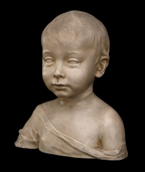 photo of plaster cast sculpture of boy from shoulders up with light tunic slipping off left shoulder with black background