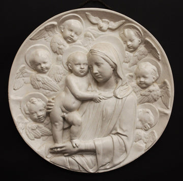 photo with black background of plaster cast relief of Madonna holding the Baby Jesus who's standing on her lap, and Angels encircling the round plaque