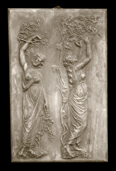 photo with black background of yellowed plaster cast relief sculpture of two robed female figures touching tree branches above their heads