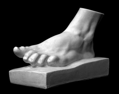 Photo of plaster cast sculpture of male foot on a thick panel at a three quarter view on a black background