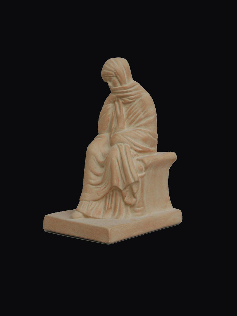 photo with a black background of a plaster cast sculpture of a seated female figurine painted terra cotta