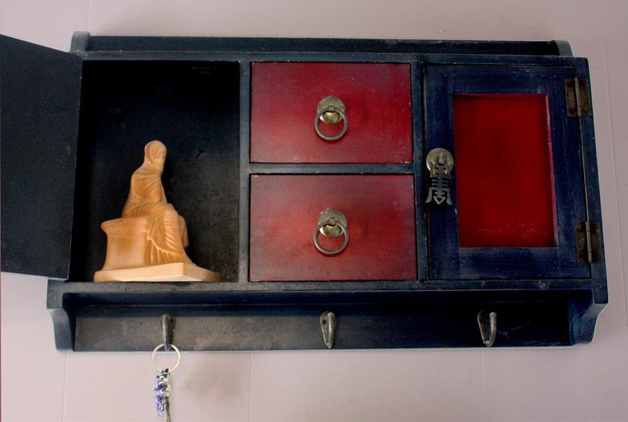 Photo of a plaster cast of a seated female figurine painted terra cotta on a small Chinese cabinet hanging on the wall