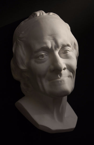 Photo with black background of plaster cast sculpture of elderly male head