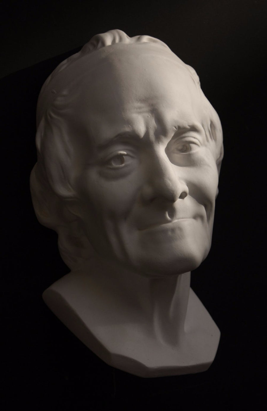 Photo with black background of plaster cast sculpture of elderly male head, namely Voltaire