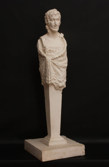 photo with black background of plaster cast sculpture of robed satyr figure with pedestal instead of legs