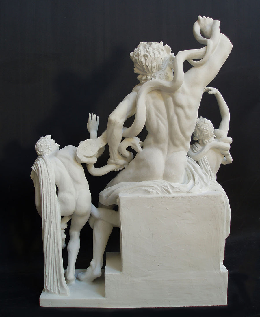 photo with black background of plaster cast sculpture from the back of partially nude male figure, namely Laocoon, and two nude young men being attacked by serpents which twist in and out of the three figures