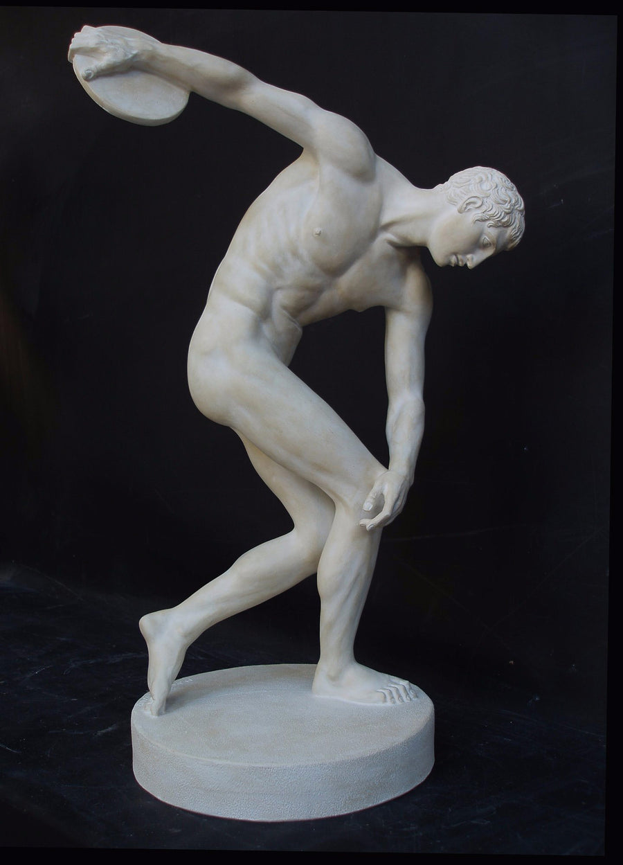 Photo with black background of plaster cast of nude male athlete readying to throw a discus