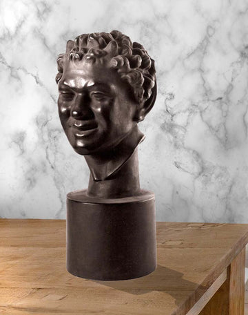Photo of plaster cast sculpture of faux bronze faun head on wooden table with marble wall behind