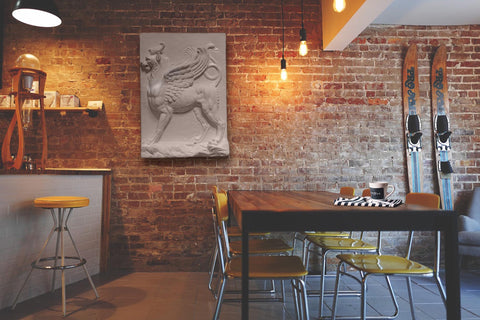 Photo of Plaster Cast of Griffin on a brick wall in a chic restaurant with a bar, table, and skis leaning against the wall