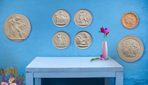 Photo of 7 Round Plaster Cast Relief Sculptures on a blue wall above a desk with a vase and pink flower