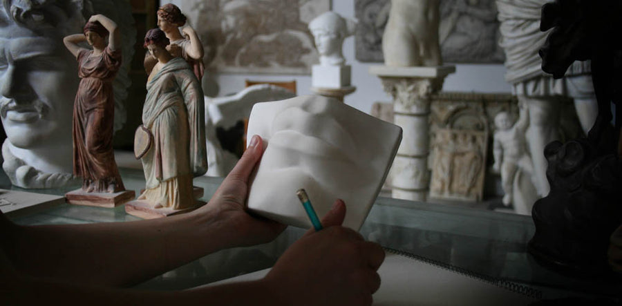Photo of a woman's left hand holding the plaster cast of David's mouth by Michelangelo and right hand holding a drawing pencil with sculptures and a sketchpad in the background