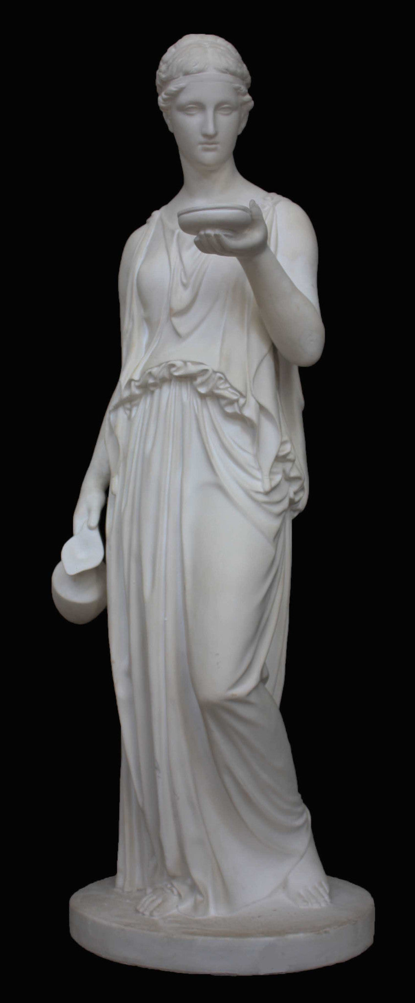photo with black background of plaster cast sculpture of goddess Hebe in robes standing and holding a jug in right hand at her side and a bowl in left hand raised in front of her