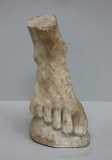 photo of yellowed plaster cast sculpture of right foot on curved surface on gray background